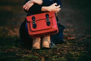 ragazza alla moda in scarpe marroni e un cappotto caldo seduto nel parco con una borsa rossa. foto