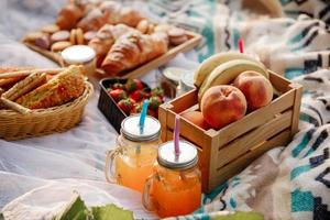 picnic al parco. frutta fresca, bevande frizzanti ghiacciate e croissant in una calda giornata estiva. pranzo al sacco. messa a fuoco selettiva. foto
