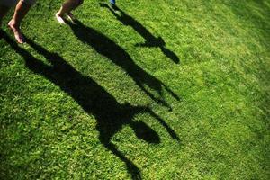 sagoma di tre persone in piedi con le mani tese sull'erba verde foto