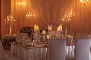 tavolo festivo decorato con fiori, stoffa e candelabri. decorazione di nozze di lusso con luci. messa a fuoco selettiva. foto