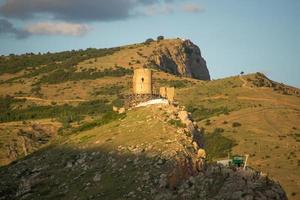 vista della fortezza genovese sul lato di una montagna con un cielo blu nuvoloso in crimea foto