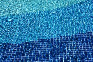 caustiche del fondo del mosaico della piscina acqua di mare increspata. flusso con onde, sport e concetto di relax. sfondo estivo. la consistenza della superficie dell'acqua. vista dall'alto. foto