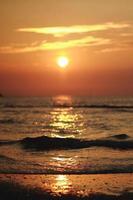 bellissimo tramonto arancione brillante su una spiaggia, senza immagine di filtro. vista incredibile con il mare del nord al tramonto foto