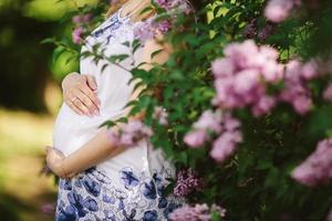 donna incinta contro albero in fiore in primavera foto
