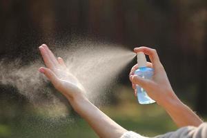 primo piano delle mani della donna applicando spray alcolico o spray antibatterico all'aperto per prevenire la diffusione di germi, batteri e virus, tempo di quarantena, concentrarsi sulle mani ravvicinate. coronavirus.