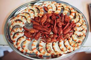 tavola festiva con gamberi pronti e gamberi con condimento su un vassoio di metallo foto