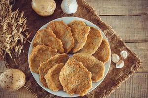 frittelle di patate cibo ucraino su un piatto e forchetta su sfondo di lino foto