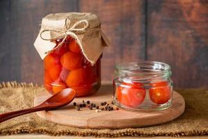 pomodori in salamoia in un barattolo di vetro su fondo in legno foto