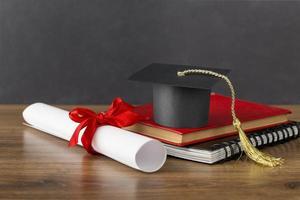 cappello di laurea e diploma sulla scrivania foto