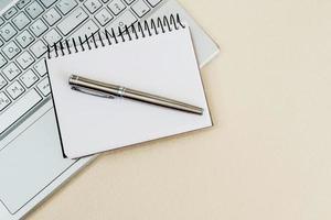 vista dall'alto di una scrivania con laptop, taccuino e penna. foto