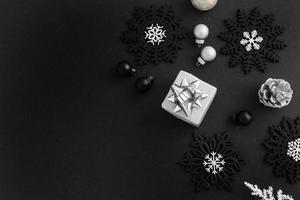 regali e fiocchi di neve su sfondo nero foto