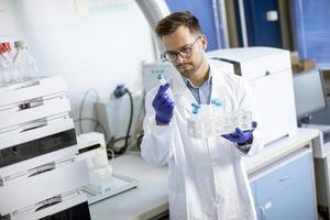giovane ricercatore che lavora con campioni chimici in laboratorio con sistema hplc e apparecchiature cromatografiche foto