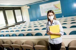 studentessa che indossa maschera medica protettiva per il viso per la protezione da virus in piedi in aula foto