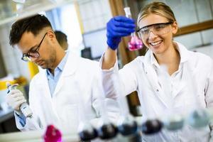 giovane scienziato femminile esaminando liquido nel laboratorio biochimico foto