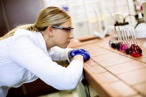 scienziato femminile in camice bianco analizzando campioni liquidi nel laboratorio biomedico foto