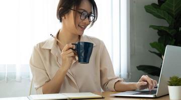 donna che tiene la tazza di caffè mentre si lavora foto