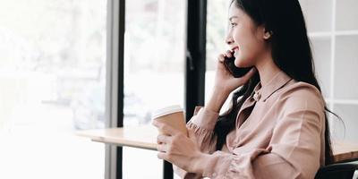 donna che parla su un telefono e che tiene un caffè foto
