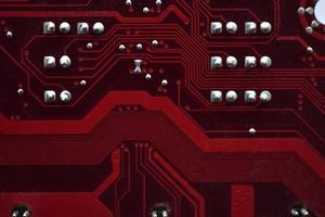 primo piano rosso dei chip della scheda madre del computer con i contatti foto