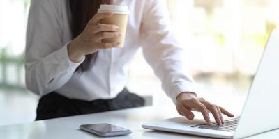 professionale tenendo il caffè durante la digitazione foto