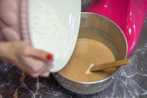 mani della donna che versano farina in una ciotola di metallo per mixer foto