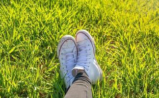 piedi della ragazza in scarpe da ginnastica bianche seduto in un prato verde foto