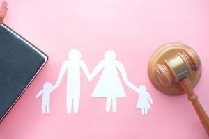 ritaglio di carta di una famiglia su uno sfondo rosa con un martelletto foto