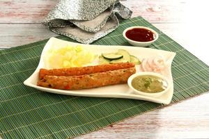 un colpo perfetto di seekh piatto non vegetariano con salsa, menta, mais, verdure su un tavolo