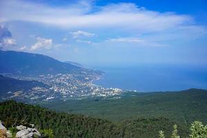 paesaggio lontano di colline, un cielo blu nuvoloso, il mar nero e Yalta, Crimea foto