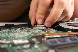 primo piano di una persona che ripara un computer portatile foto