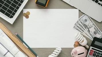vista dall'alto di carta bianca sulla scrivania con soldi, salvadanaio e calcolatrice foto