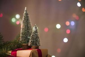 scatola regalo alberi di Natale decorativi e bokeh luce foto