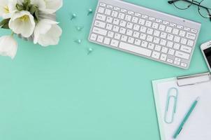 desktop con computer su sfondo verde acqua foto