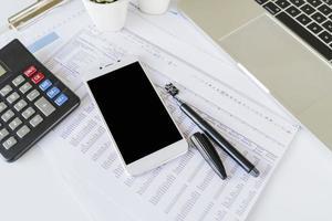 scrivania di ufficio ragioniere con calcolatrice e smartphone foto