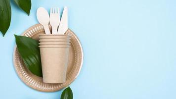 piatti usa e getta con tazze e posate su sfondo blu copia spazio foto