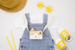disposizione piatta di vestiti per bambini con macchina fotografica foto