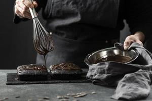 vista frontale del pasticcere che prepara la torta al cioccolato foto