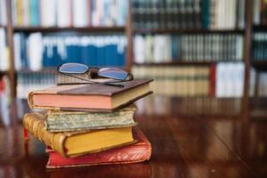 occhiali da vista e vecchi libri sul tavolo della biblioteca foto