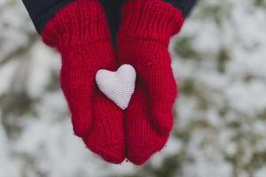 mani guantate che tengono cuore bianco foto