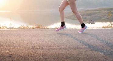 giovane donna che indossa scarpe sportive in esecuzione su strada asfaltata foto