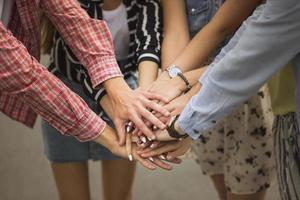 amici del primo piano che mettono le mani insieme foto