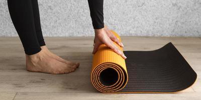 mani del primo piano che tengono la stuoia di yoga foto