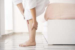 mani del primo piano che massaggiano le gambe foto