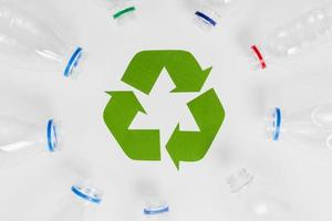 bottiglie di plastica vuote intorno all'icona di riciclaggio foto
