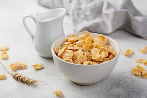 colazione ad angolo alto di cereali di mais in una ciotola con il latte foto
