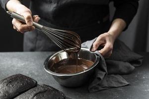pasticcere di alto angolo che prepara la torta al cioccolato foto