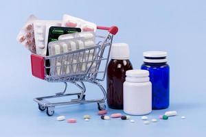 oli di pinna di pillola ad alto angolo e contenitori di plastica con carrello della spesa in miniatura su sfondo blu foto