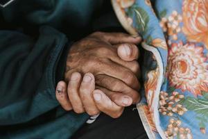 senzatetto che tiene le mani con la coperta foto