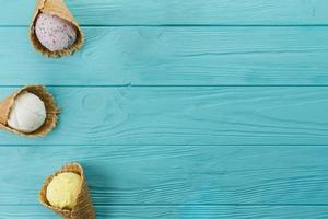 coni gelato con gusti diversi sulla tavola di legno blu foto