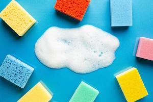 spugne colorate piatto di schiuma giaceva su sfondo blu foto