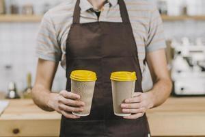 barista ritagliata con bevande calde di fronte alla telecamera foto